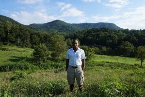 Kevin standing outdoors with view of mountain, rolling hills, and lots of green